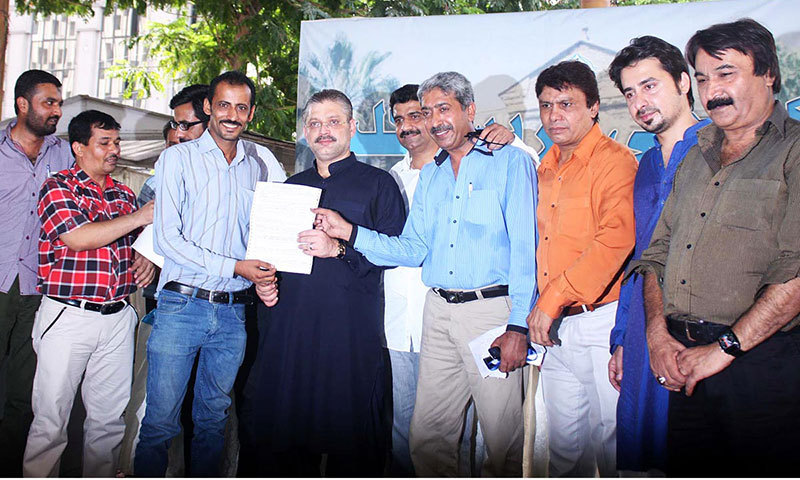 Provincial Minister for Information Sharjeel Inaam Memon distributing challans of plots given to members of Karachi Press Club. — Photo by Online