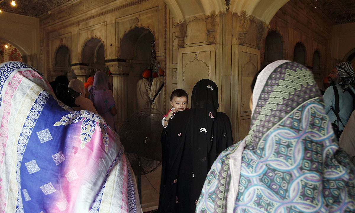 A female Sikh pilgrim (C) carrying a child visits Maharaja Ranjit Singh's mausoleum with others in Lahore June 29, 2014. — Photo by Reuters
