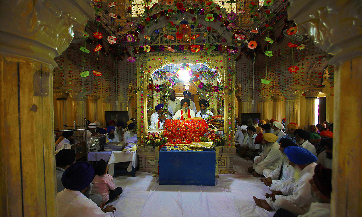 Sikh pilgrims attend a prayer session inside the compound of Maharaja Ranjit Singh's mausoleum in Lahore June 29, 2014.— Photo by Reuters
