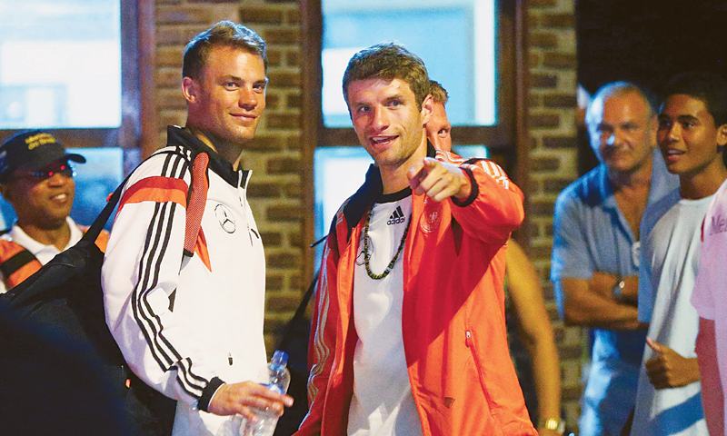 GERMANY'S goalkeeper Manuel Neuer (L) listens to team-mate Thomas Mueller in the town of Santa Cruz Cabralia, north of Porto Seguro.—Reuters