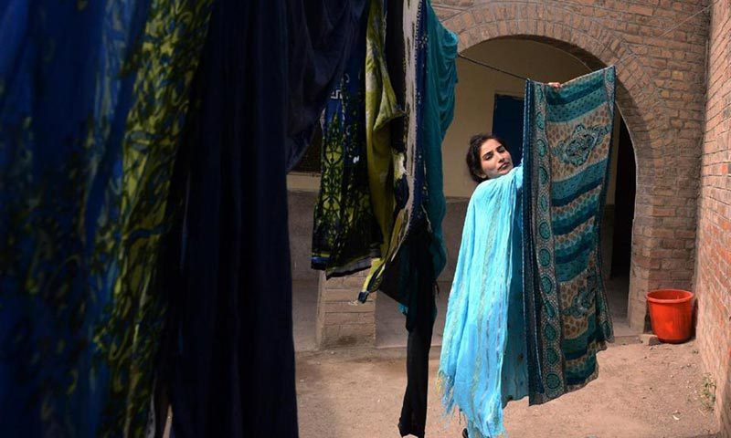 A Pakistani Christian resident displaced by a military operation in the North Waziristan tribal agency hangs clothes to dry as she seeks temporary shelter at a school in Bannu. — Photo by AFP