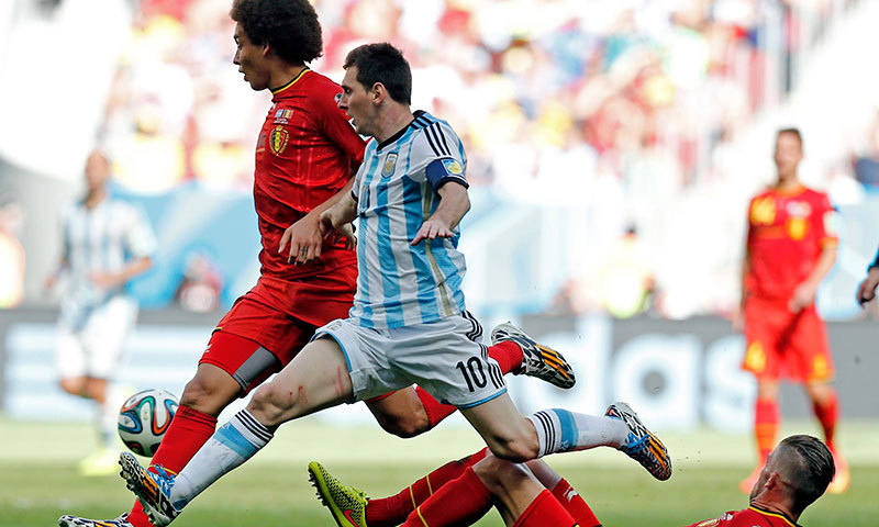 Argentina's Lionel Messi leaps in unison with Belgium's Axel Witsel as they chase the ball. – AP Photo