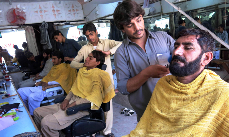 OCUS BY SHAUKAT KHATTAK Internally displaced Pakistan civilians fleeing from a military operation against Taliban militants in the North Waziristan tribal agency receive haricuts at a barbershop in the neighbouring town of Bannu on July 6, 2014. Photo AFP