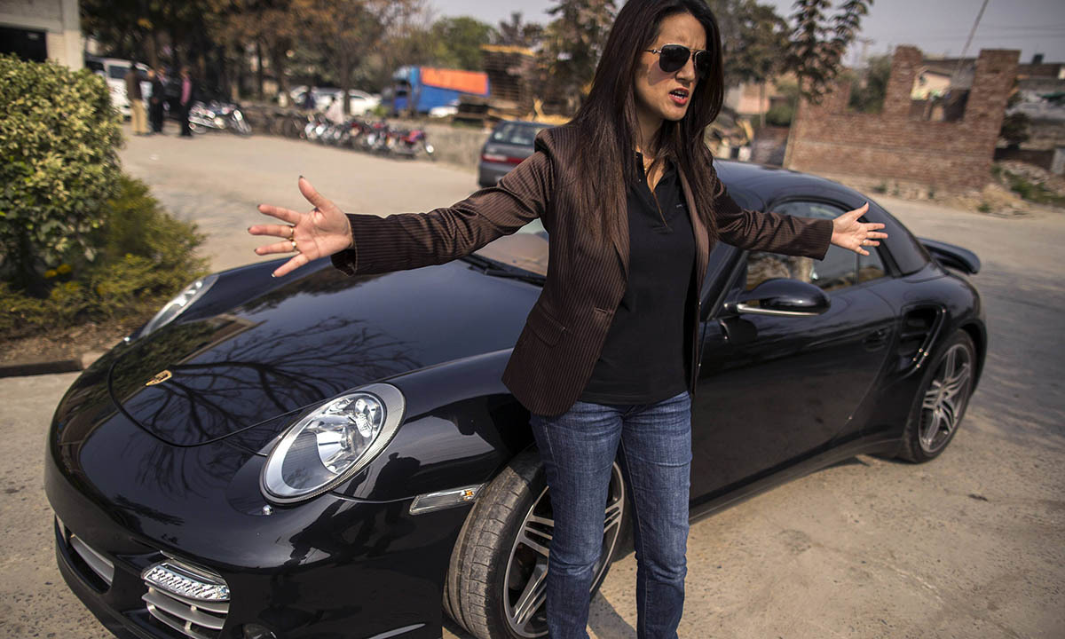 Ansa Hasan, a marketing manager at Porsche Pakistan, gestures as she prepares for an upcoming event, outside the Porsche showroom in Lahore February 21, 2014.