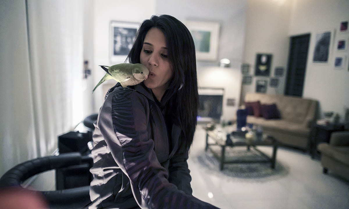 Ansa Hasan, a marketing manager at Porsche Pakistan, plays with a parrot at her house in Lahore February 21, 2014.