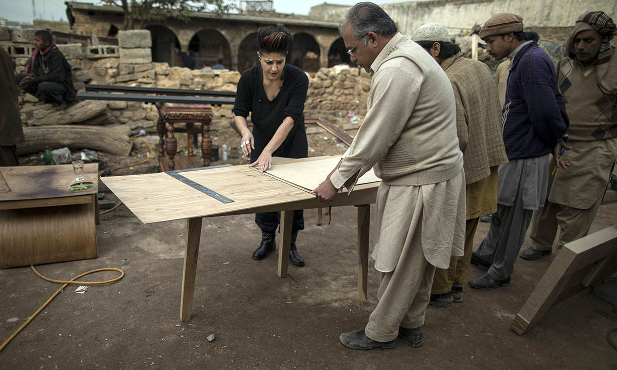 Interior designer Zahra Afridi (L) talks to a carpenter at a workshop on the outskirts of Islamabad February 10, 2014.