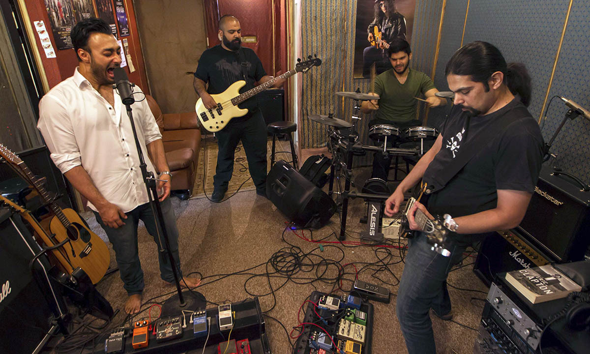 Lead guitarist and songwriter, Khurram Waqar (R), vocalist Umair Jaswal (L), bass guitarist Rahail Siddiqui (2nd L), and drummer Asfendyar Ahmad of the rock band Qayaas rehearse at a private studio in Islamabad April 30, 2014. The band feels that the current security situation has hampered the country's music scene. Most of the band's performances are at schools, colleges or private festivals.