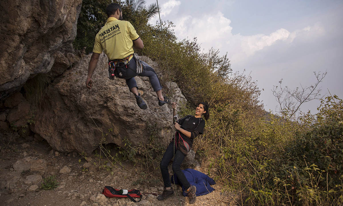 Rock climber Nazia Parveen (R) jokes with her trainer Imran Junaidi during their practice in Islamabad February 15, 2014.