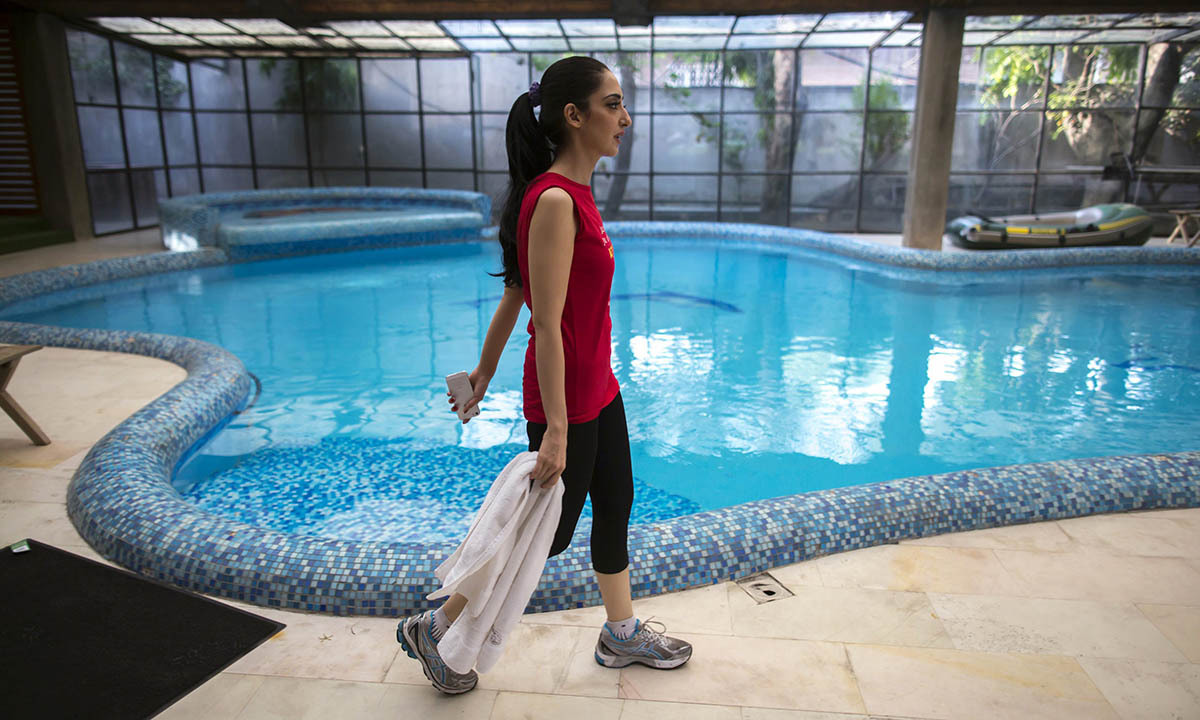 Fatima walks past the swimming pool after working out in her gym at her house in Lahore May 28, 2014.