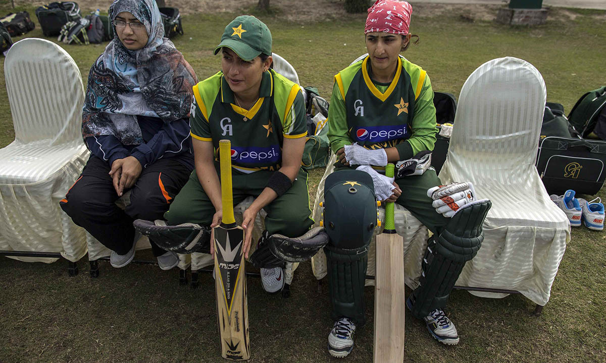 Sana Mir (C), captain of Pakistan's women's cricket team, sits with a physical therapist (L) and a team-mate during a training session in preparation for the 2014 International Cricket Council (ICC) World Twenty20 competition in Muridke February 22, 2014.