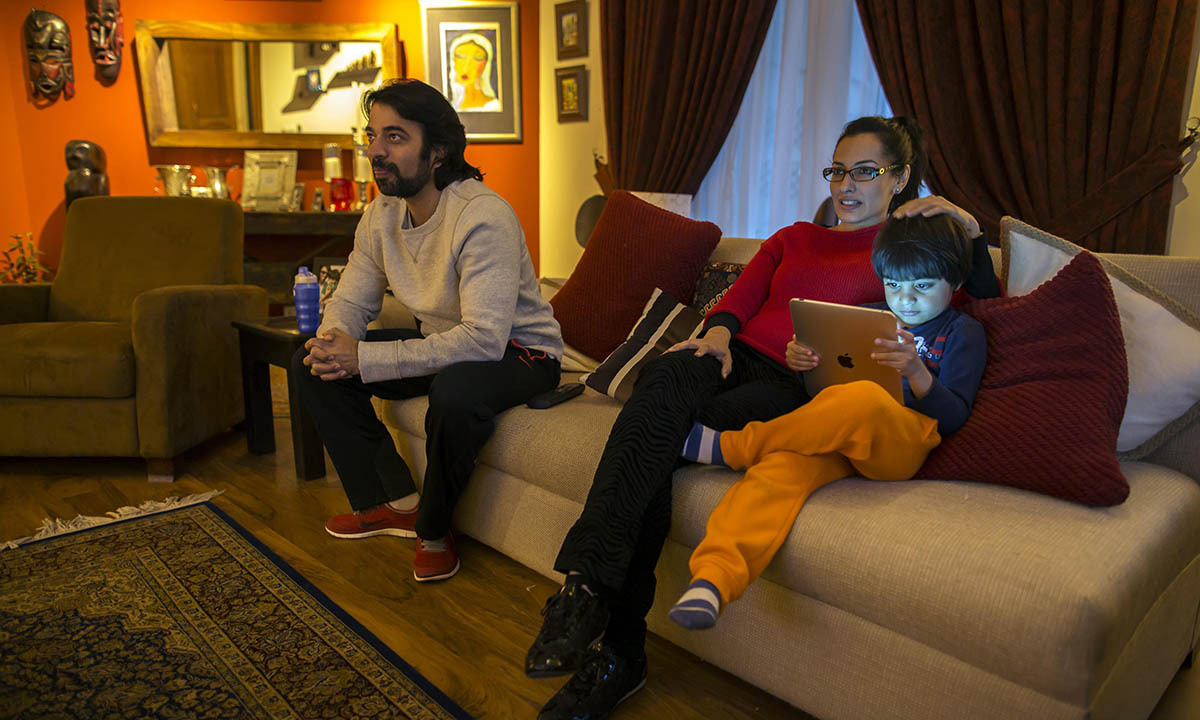 Naadiya Manzur (C), watches television with her husband Omar and son Zidaan at her house in Islamabad March 8, 2014.