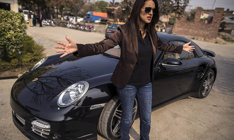 Ansa Hasan, a marketing manager at Porsche Pakistan, gestures as she prepares for an upcoming event, outside the Porsche showroom in Lahore February 21, 2014. Though instability continues to plague Pakistan and many areas are dominated by social conservatism, some of the country's more affluent residents have worked to fashion a very different kind of lifestyle for themselves. Pictures of men and women taking part in all sorts of activities and professions - from being a pilates instructor, to a textile retail entr