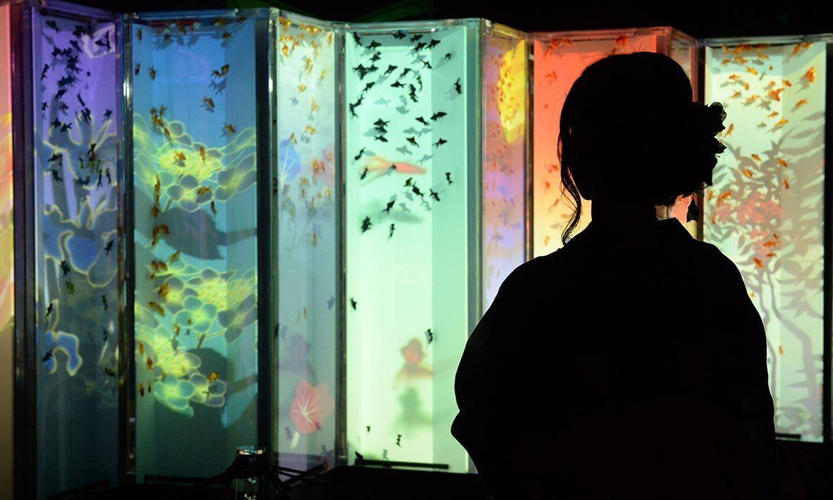 "A young woman wearing the summer Kimono, ""Yukata"" watches the folding screen featuring goldfish during the press preview of ""Eco Edo Nihonbashi Art Aquarium 2014"" exhibition in Tokyo. -AFP Photo"