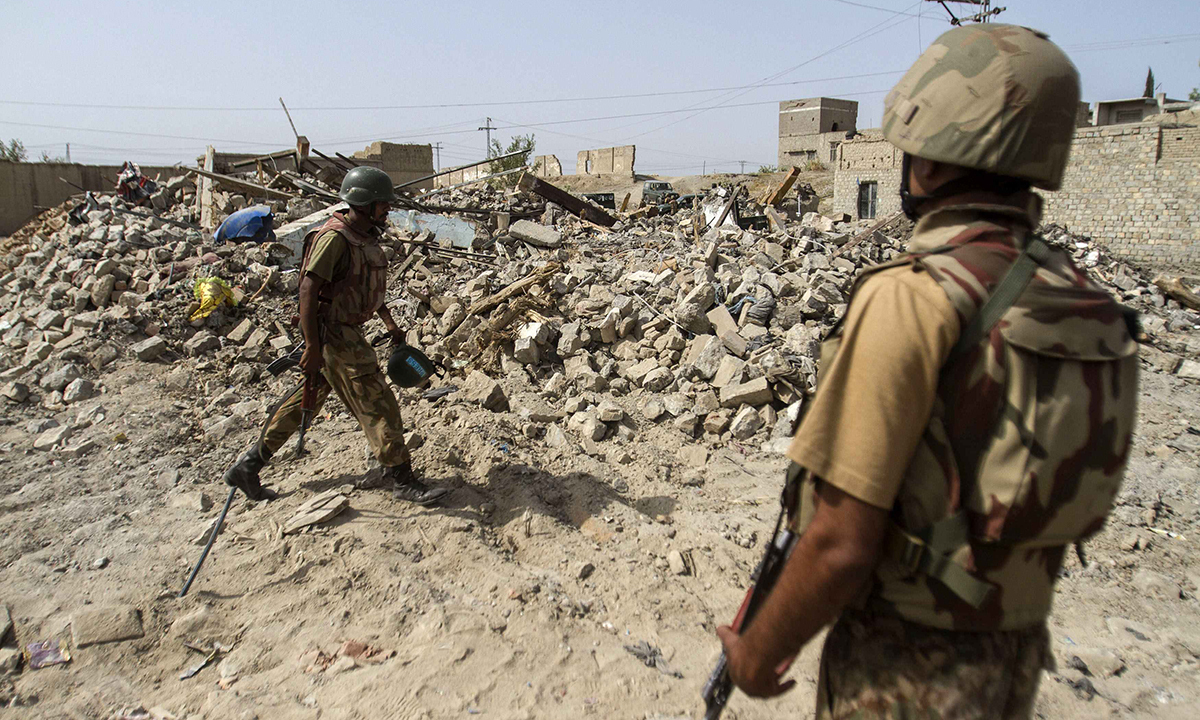 Soldiers stand near the debris of a house which was destroyed during a military operation against Taliban militants in the  town of Miramshah in North Waziristan July 9, 2014.— Photo by Reuters