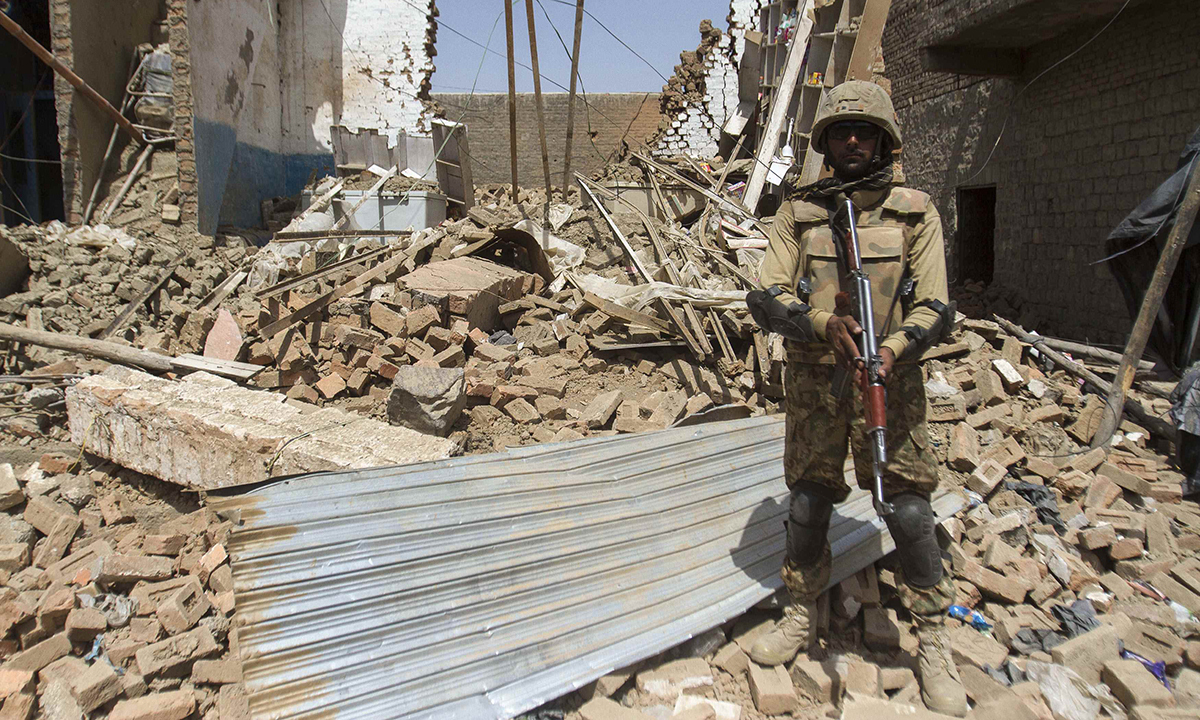 A Pakistani soldier stands beside a house which was destroyed during a military operation against Taliban militants, in the town of Miranshah, North Waziristan July 9, 2014. The Pakistani military has seized control of 80 percent of Miranshah, the capital of the remote North Waziristan tribal region where the military launched an operation against Islamist militants last month, a general said Wednesday. Picture taken July 9, 2014.   REUTERS/Maqsood Mehdi (PAKISTAN - Tags: POLITICS MILITARY CIVIL UNREST)