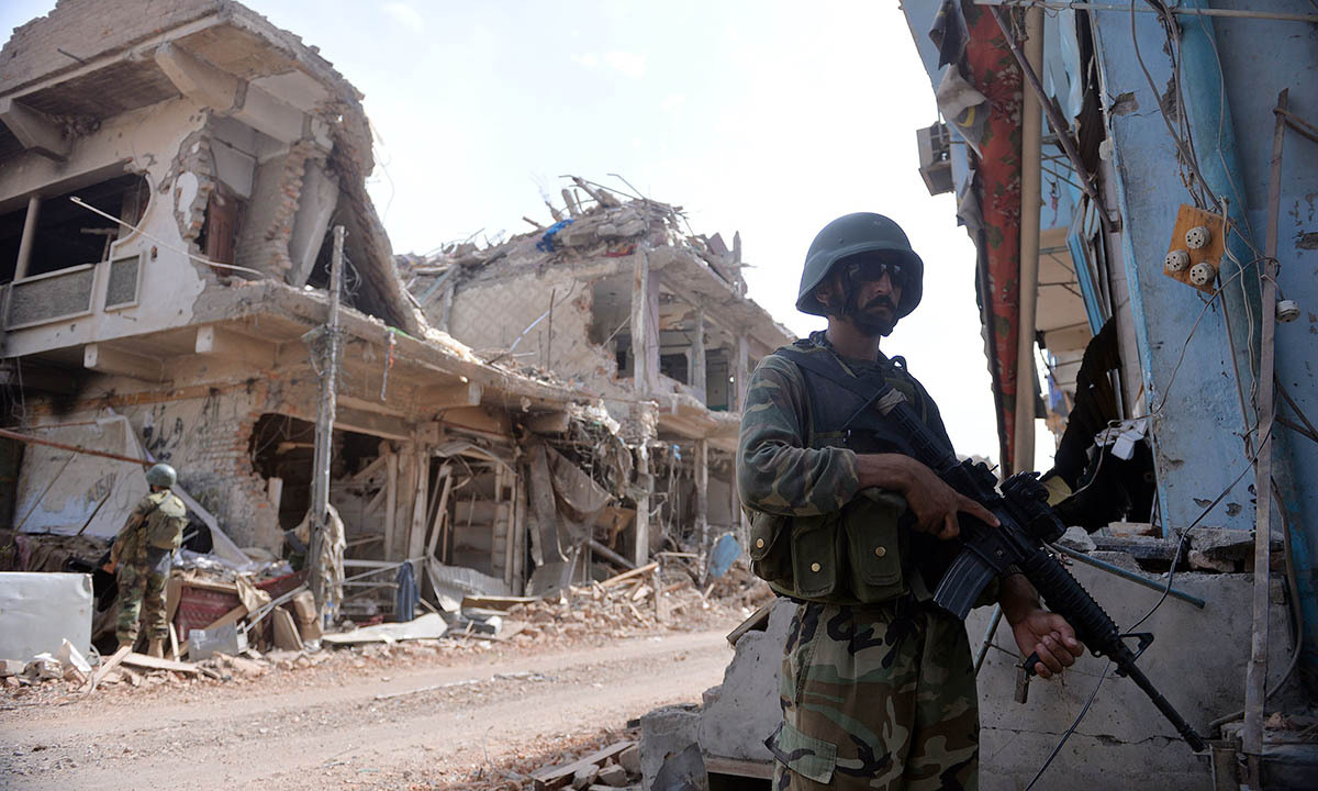Pakistani soldiers stand guard at a destroyed empty bazaar during a military operation against Taliban militants in the main town of Miranshah in North Waziristan on July 9, 2014. Last month Pakistan's military launched a long-awaited offensive in North Waziristan, aimed at wiping out longstanding militant strongholds in the area, which borders Afghanistan. More than 800,000 people have fled a major military offensive against the Taliban in a Pakistani tribal area, officials said Wednesday. AFP PHOTO/Aamir QURESHI