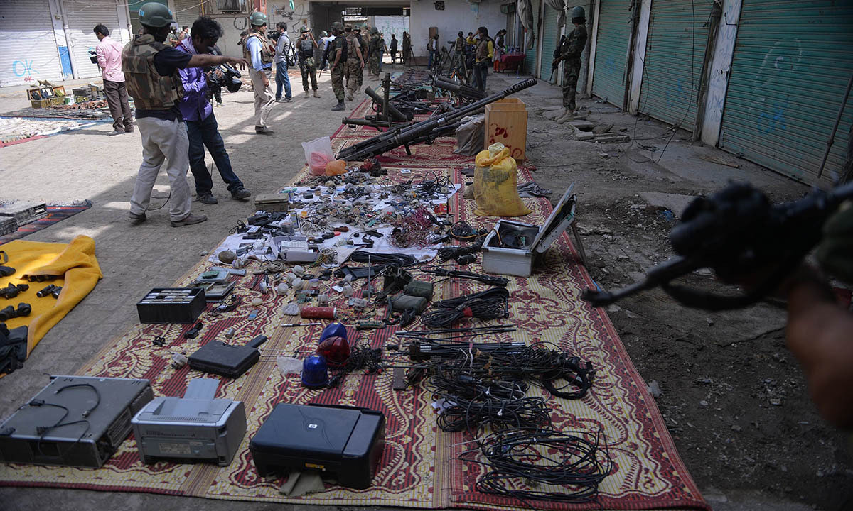 Pakistani media personnel take footage of seized weapons at an empty bazaar during a military operation against Taliban militants in the main town of Miranshah in North Waziristan on July 9, 2014. Last month Pakistan's military launched a long-awaited offensive in North Waziristan, aimed at wiping out longstanding militant strongholds in the area, which borders Afghanistan. More than 800,000 people have fled a major military offensive against the Taliban in a Pakistani tribal area, officials said Wednesday. AFP PHO