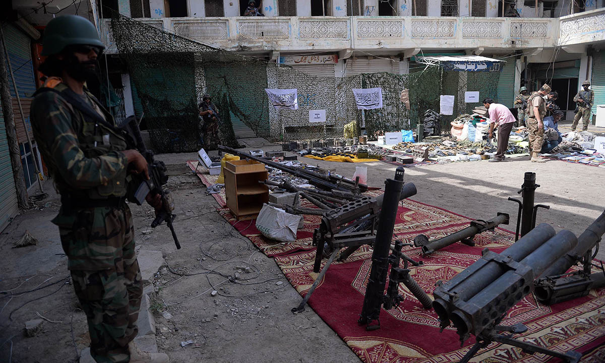 Pakistani soldiers stand beside seized weapons at an empty bazaar during a military operation against Taliban militants in the main town of Miranshah in North Waziristan on July 9, 2014. Last month Pakistan's military launched a long-awaited offensive in North Waziristan, aimed at wiping out longstanding militant strongholds in the area, which borders Afghanistan. More than 800,000 people have fled a major military offensive against the Taliban in a Pakistani tribal area, officials said Wednesday. AFP PHOTO/Aamir Q