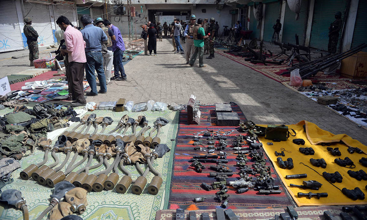 Media personnel take footage of seized weapons at an empty bazaar during a military operation against Taliban militants in the main town of Miramshah in North Waziristan on July 9, 2014. — Photo by AFP