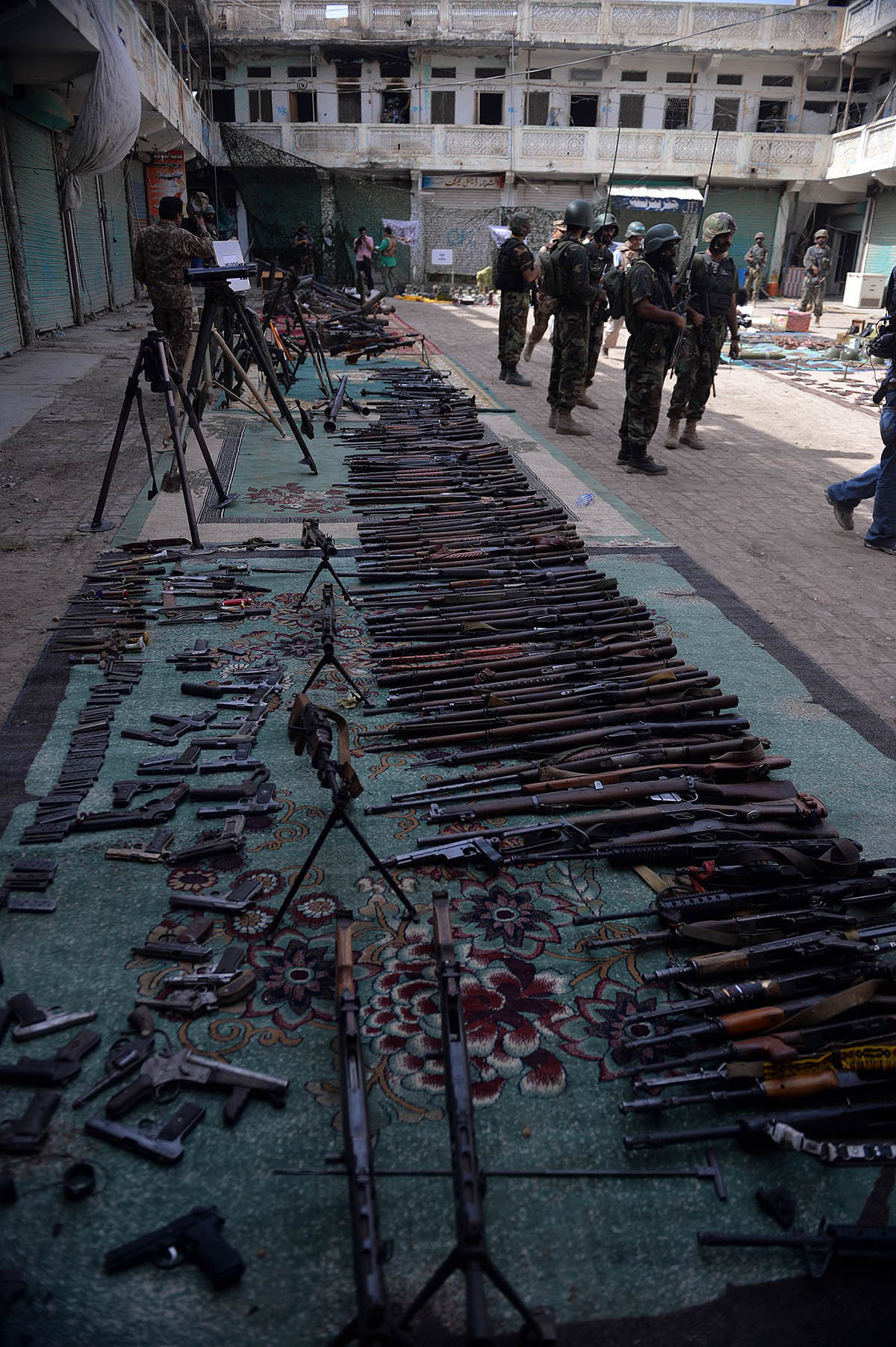 Pakistani soldiers stand by seized weapons at an empty bazaar during a military operation against Taliban militants in the main town of Miranshah in North Waziristan on July 9, 2014. Last month Pakistan's military launched a long-awaited offensive in North Waziristan, aimed at wiping out longstanding militant strongholds in the area, which borders Afghanistan. More than 800,000 people have fled a major military offensive against the Taliban in a Pakistani tribal area, officials said Wednesday. AFP PHOTO/Aamir QURES