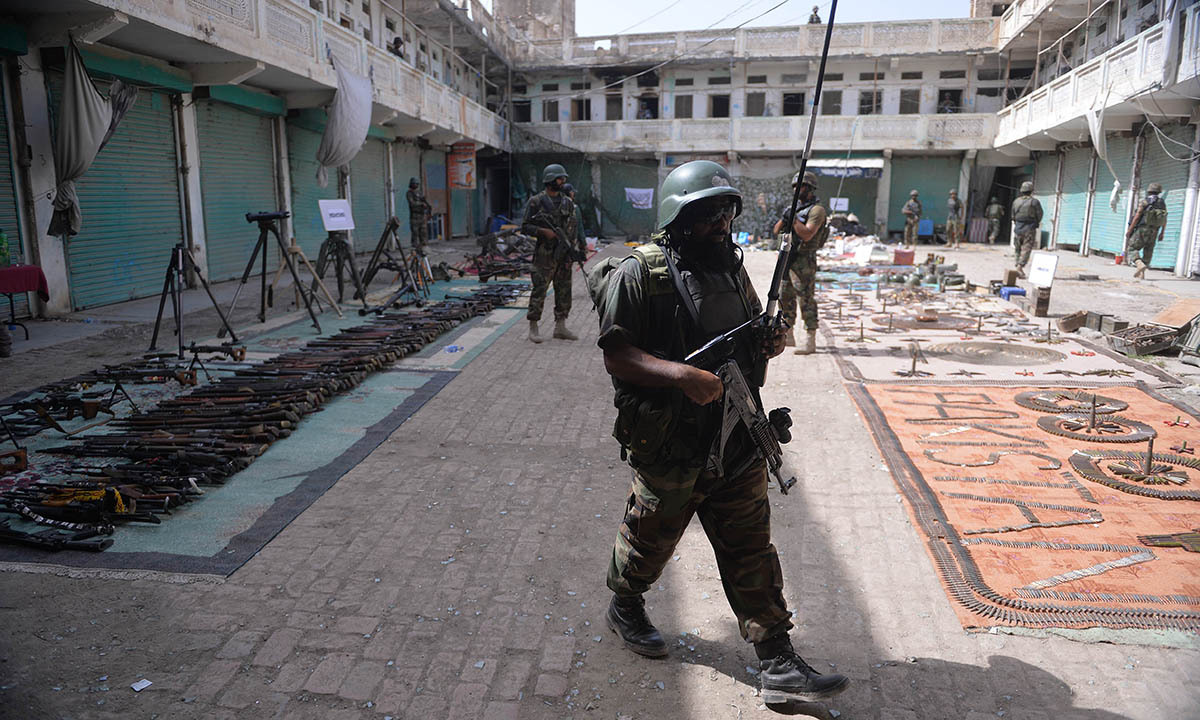 Soldiers walk past seized weapons at an empty bazaar during a military operation against Taliban militants in the main town of Miramshah in North Waziristan on July 9, 2014.— Photo by AFP
