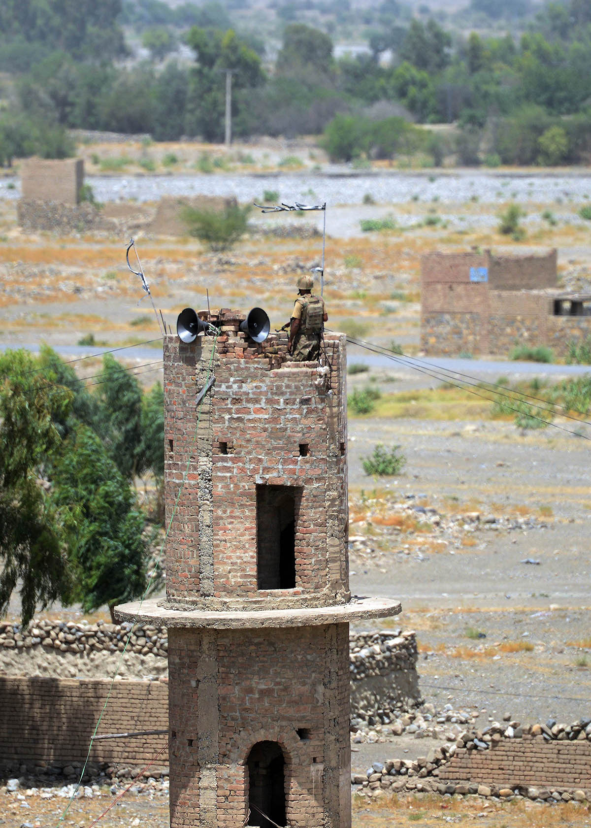 This photograph taken on July 9, 2014 shows a Pakistani soldier keeping watch on top of damaged mosque minaret during a military operation against Taliban militants, in the main town of Miranshah in North Waziristan.   Pakistan's military says its anti-militant offensive in a northwestern tribal area has now taken control of 80 percent of a strategic town, as a US drone strike on July 10 killed six suspected insurgents. AFP PHOTO/Aamir QURESHI