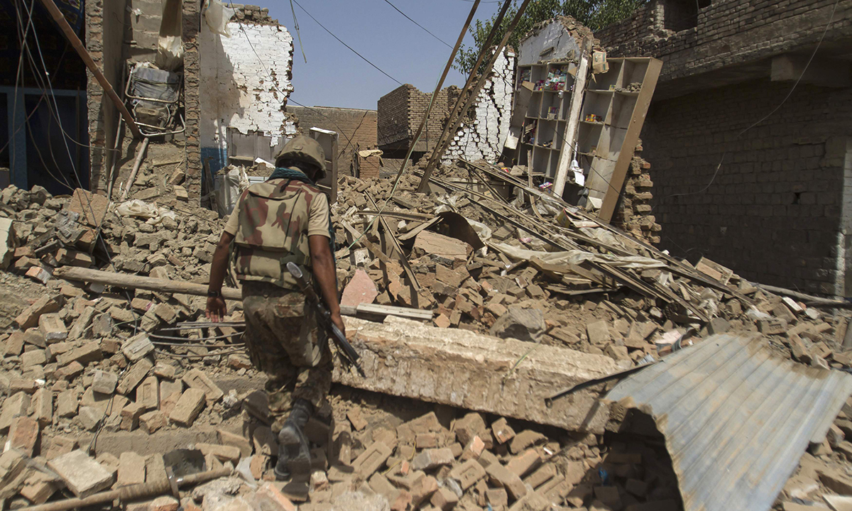 A Pakistani soldier walks at a house which was destroyed during a military operation against Taliban militants, in the of town of Miranshah, North Waziristan July 9, 2014. The Pakistani military has seized control of 80 percent of Miranshah, the capital of the remote North Waziristan tribal region where the military launched an operation against Islamist militants last month, a general said Wednesday. Picture taken July 9, 2014. REUTERS/Maqsood Mehdi (PAKISTAN - Tags: POLITICS CIVIL UNREST MILITARY)