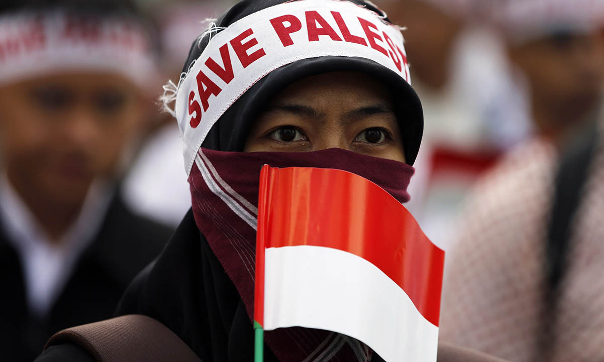 """A woman wearing a sign that reads """"Save Palestine"""" on her head, holds an Indonesian national flag as she takes part in a protest against Israel's ongoing military operation in the occupied West Bank, in Jakarta July 11, 2014.— Photo by Reuters"""