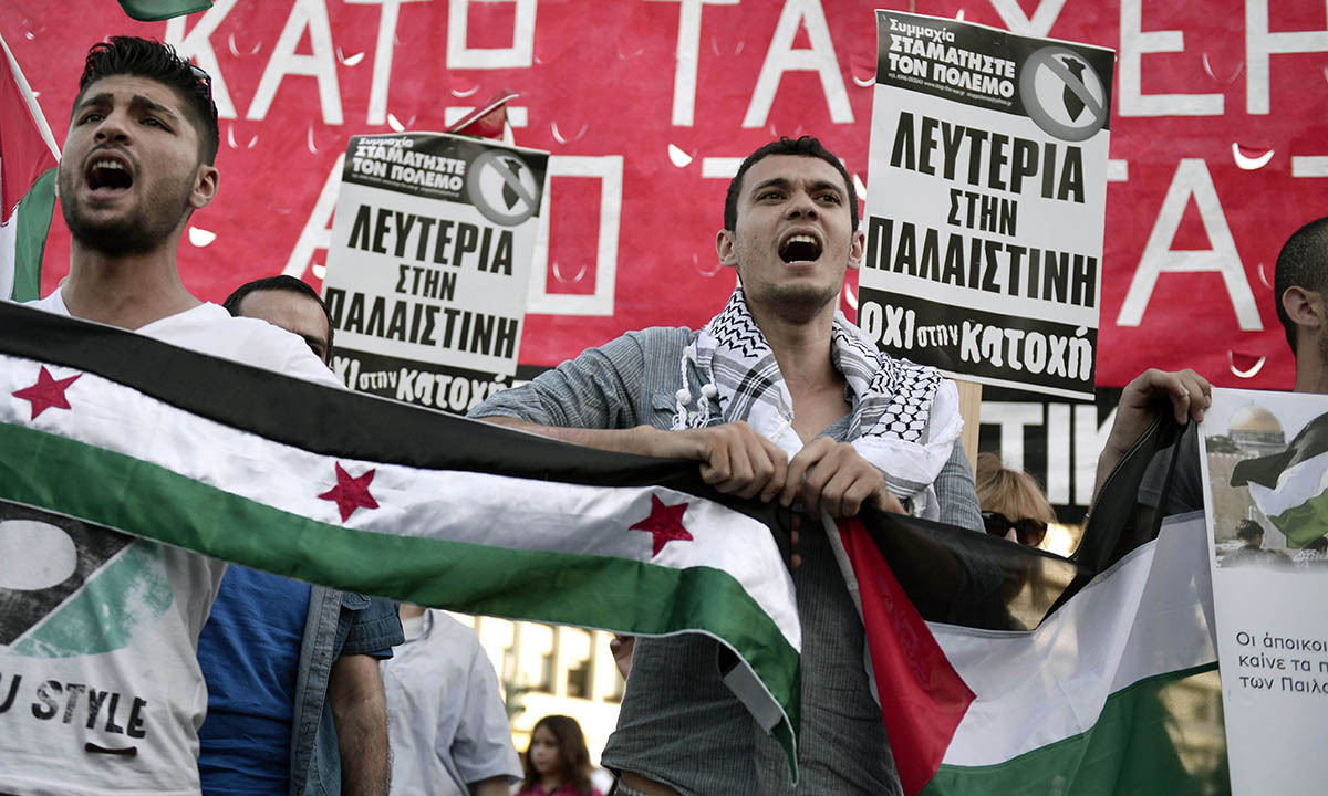 Palestinians who live in Greece shout slogans on July 10, 2014 near the Israeli embassy in Athens, during a demonstration by Palestinians and Greeks who support them against Israeli air strikes on the Gaza strip.— Photo by AFP