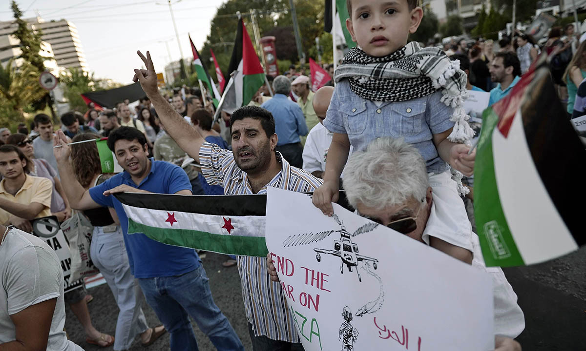 People shout slogans on July 10, 2014 near the Israeli embassy in Athens, during a demonstration by Palestinians and Greeks who support them against Israeli air strikes on the Gaza strip. — Photo by AFP