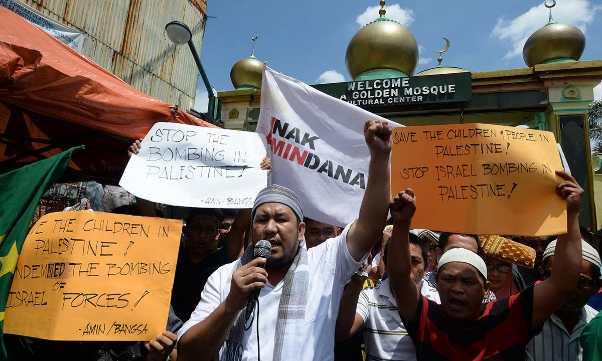Philipinos holding placards raise clinched fists as they shout during a pro-Palestine protest after Friday prayers outside the Golden mosque in Quiapo district of Manila on July 11, 2014. The protesters condemned Israel over the bombings of Gaza.  — Photo by AFP