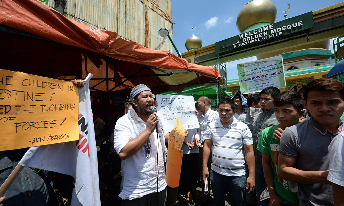 A Phillipino speaks next to a placard during a pro-Palestine protest after Friday prayers outside the Golden mosque in Quiapo district of Manila on July 11, 2014, while other Muslims walk past them. The protesters condemned Israel over the bombings of Gaza.  — Photo by AFP