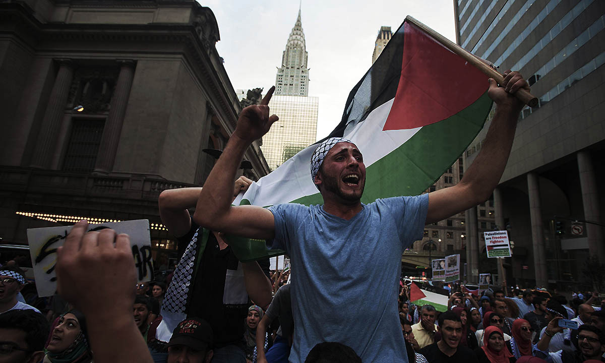 """A man waves the Palestinian national flag as he shouts, """"Free Palestine"""", during a march demanding an end to the escalating Israeli-Palestinian hostilities in that region, in midtown Manhattan, New York July 9, 2014. The Chrysler Building (C) is seen in the background.  — Photo by Reuters"""