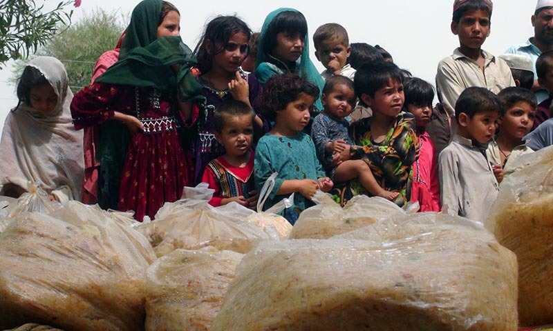 Children wait in a line to recveive food in the sweltering heat at a relief camp. —Photo by Zahir Shah Sherazi