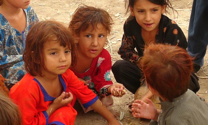 IDP children sit on dirt while sharing a meal.— Photo by Zahir Shah