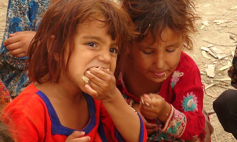 A young girl eats the meal provided at  relief camp in Bannu. — Photo by Zahir Shah Sherazi