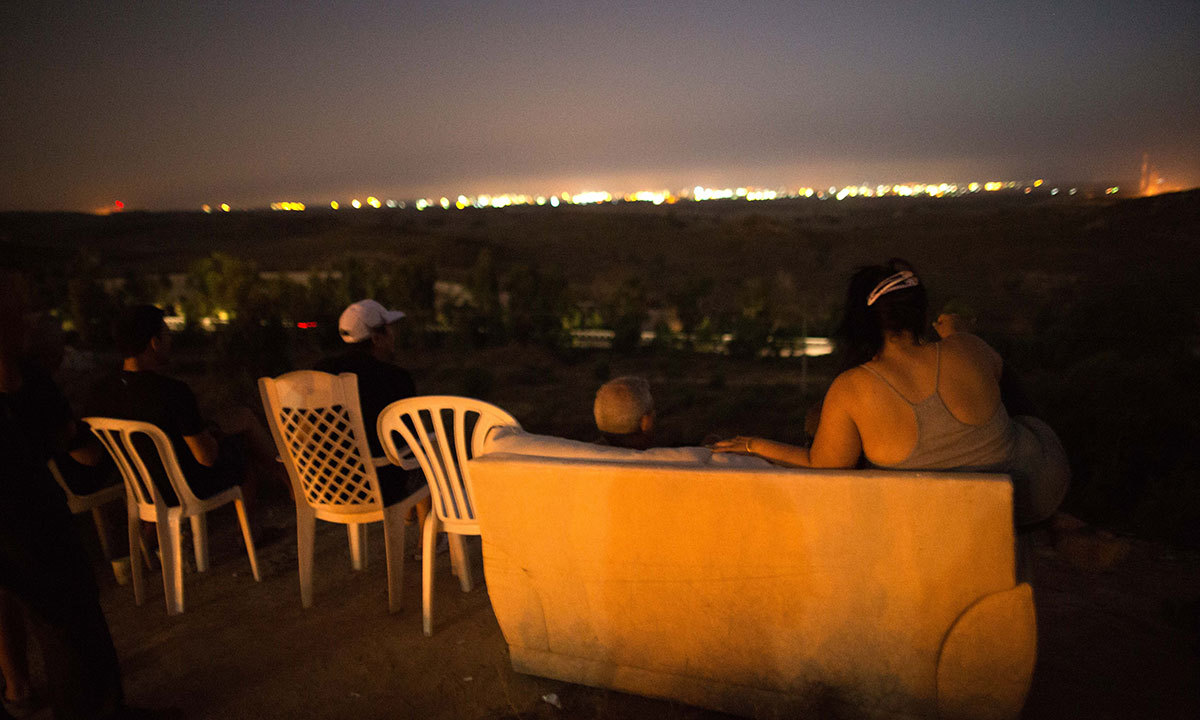 Israeli residents, mostly from the southern Israeli city of Sderot, sit on a hill overlooking the Gaza Strip, on July 12, 2014, to watch the fighting between the Israeli army and Palestinian militants. — Photo by AFP