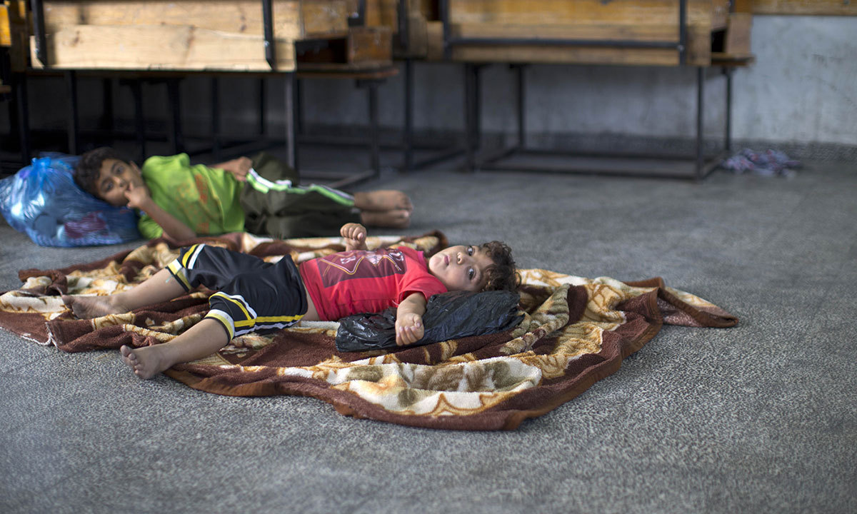 This picture shows Palestinian children asleep on the floor at a UN school after evacuating their home near the border in Gaza City on July 13, 2014. Israeli marines mounted a first ground assault on Gaza, further escalating a deadly six-day offensive hours after the UN Security Council unanimously called for a ceasefire. — Photo by AFP