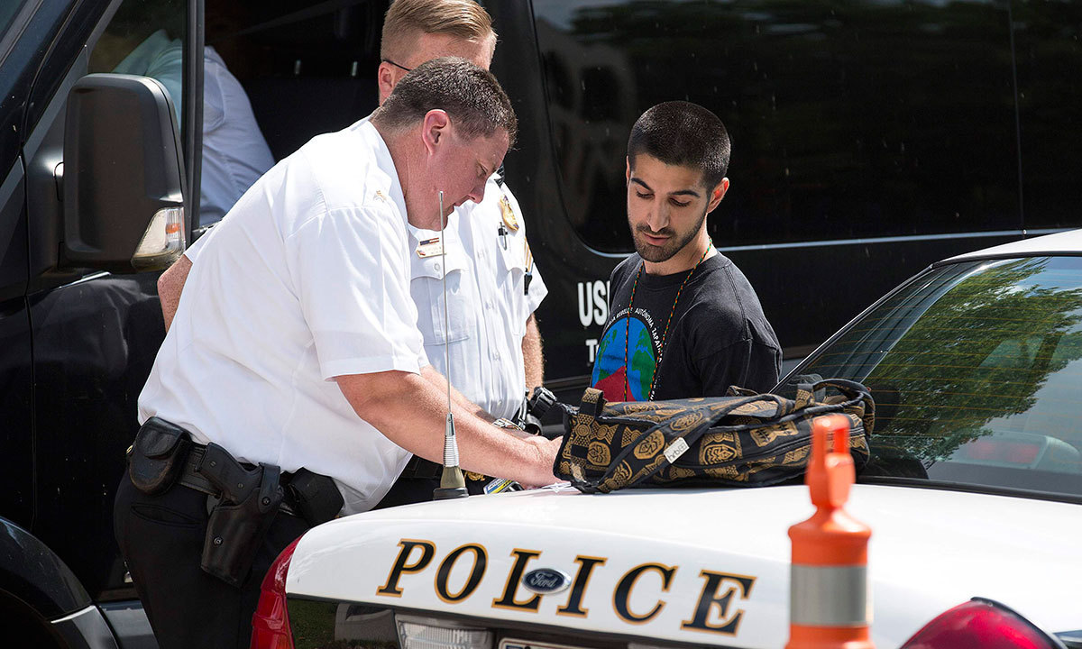 Police question a protester after he was detained during a demonstration calling for an end to the Israeli airstrikes on Gaza in front of the Israeli Embassy in Washington July 11, 2014. — Photo by Reuters