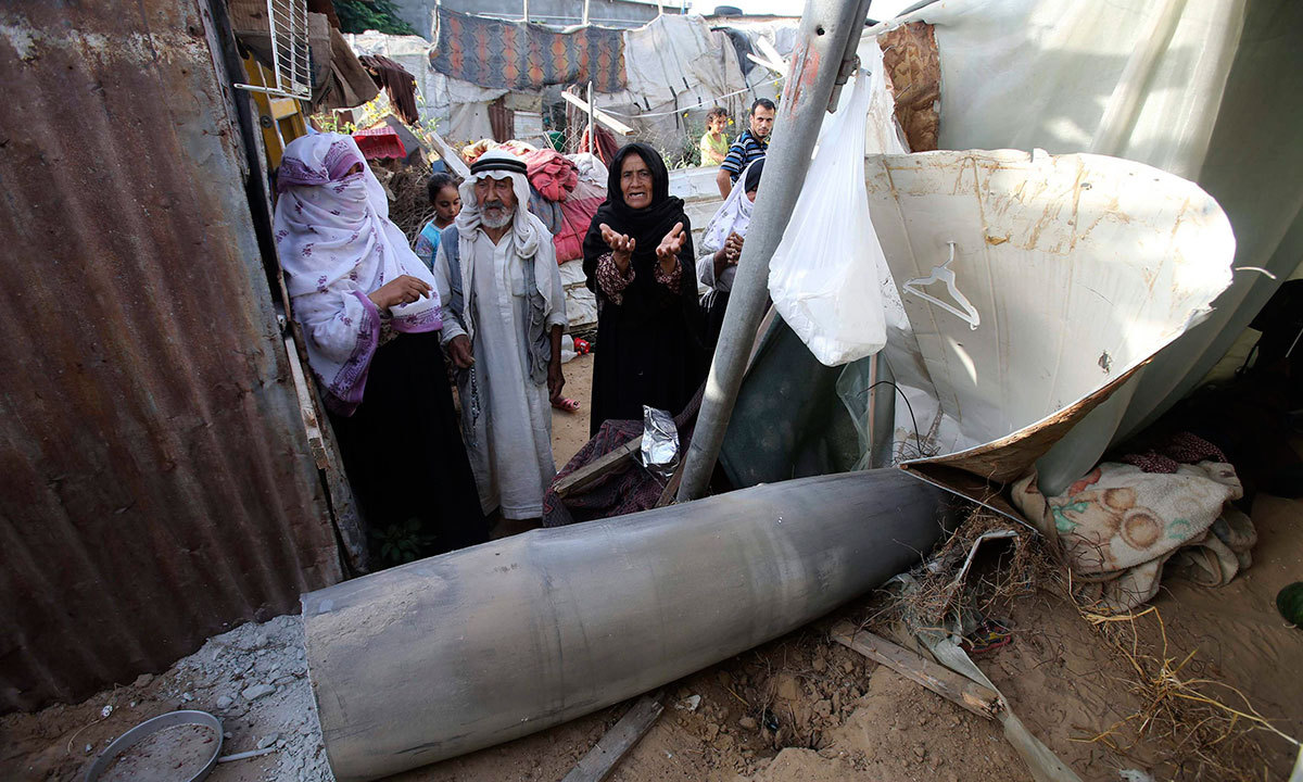 A Palestinian woman gestures as she stands behind a missile which witnesses said was fired by Israeli aircraft, at a shack belonging to Bedouins in Rafah, in the southern Gaza Strip July 13, 2014. — Photo by Reuters