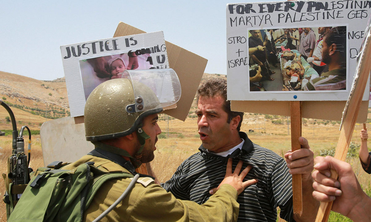 A Palestinian protester holds a picture of Gaza's victims as he argues with an Israeli army soldier during a protest against Israeli air strikes on Gaza, at Hawara checkpoint near the the West Bank city of Nablus July 12, 2014. — Photo by Reuters
