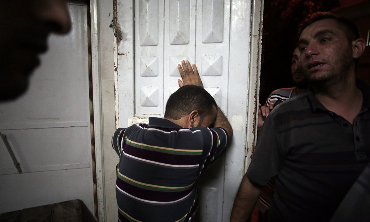 Palestinians mourn their relatives in the morgue of the Shifa hospital in Gaza City on Saturday, July 12, 2014. — Photo by AP