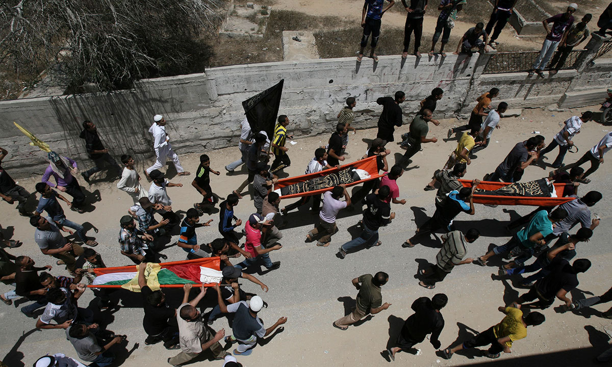 """In one telephone call, a loud boom could be heard on the line, so close the two were not sure on which side of the border fence the explosive had fallen. """"I think it's your side,"""" Mehanna told her Israeli friend. """"Hitting our side?"""" - excerpt from Washington Post report. In this picture, mourners carry bodies of Palestinian people killed in an Israeli air strike on a building near their family houses, during their funerals in Rafah refugee camp, southern Gaza Strip, Friday July 11, 2014. — Photo by AP"""