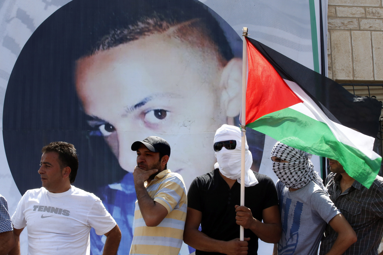 The murder of the Israeli teens sparked anger in Israel, who accused the Palestinian movement Hamas, which has its power base in the Gaza Strip, of kidnapping them. This led to the retaliatory killing of a Palestinian youth Mohammad Abu Khder, who was reportedly kidnapped and killed. In this picture, a mourner holds the national flag as mourners gather for the funeral of 16-year-old Mohammed — Photo by AFP