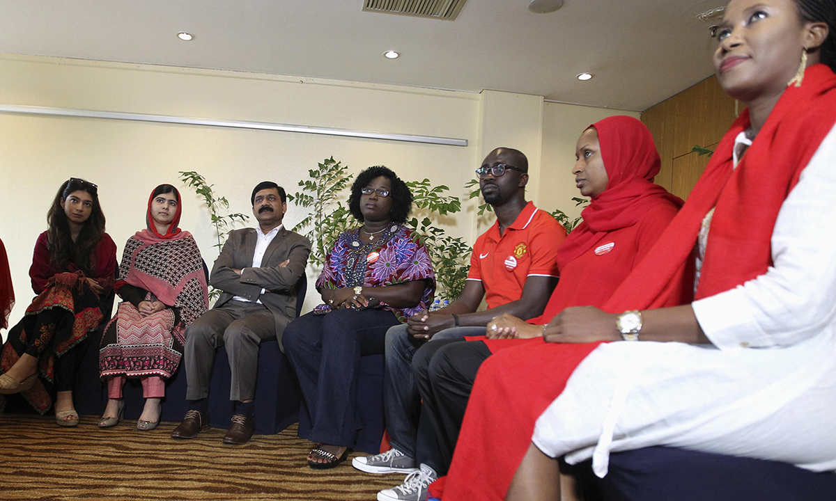 Pakistani schoolgirl activist Malala Yousafzai (2nd L) sits with her father Ziauddin Yousafzai (3rd L) and Malala Fund CEO Shiza Shahid (L) during a meeting with the leaders of the #BringBackOurGirls Abuja campaign group, in Abuja July 13, 2014. – Photo by Reuters