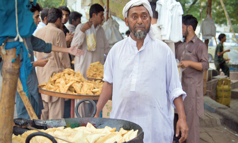 Ustad Allah Ditta, or 'Bengali' to his customers, keeps a vigilant eye on goings-on at his stall. — Photos by Faran Rafi