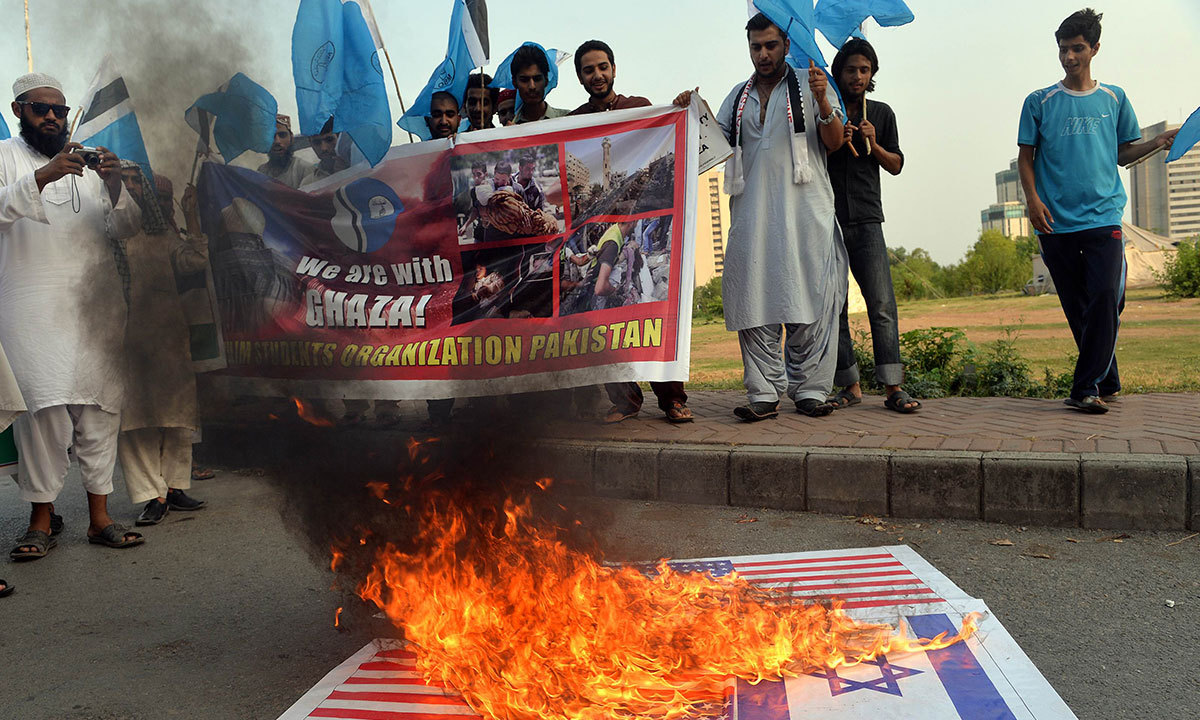 Activists of Muslim Students Organisation Pakistan look on beside burning Israeli and US flags during a demonstration against Israeli military operations in Gaza, in Islamabad on July 14, 2014. — Photo by AFP