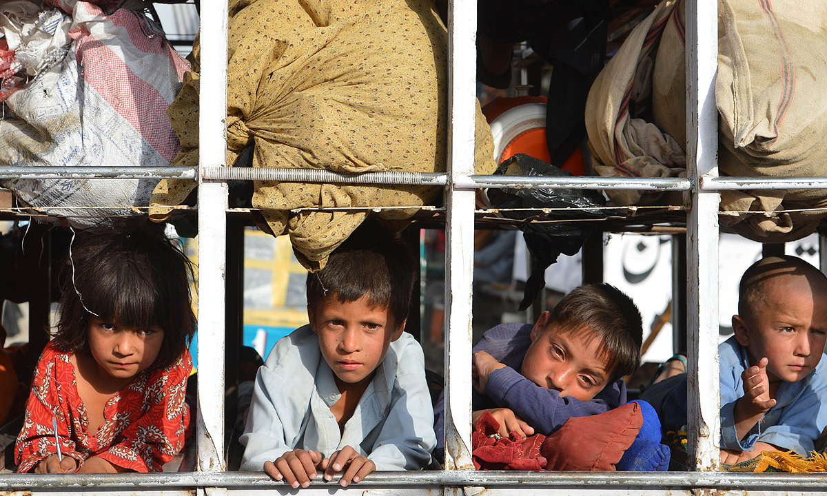 Photo shows children arriving by truck with some belongings in the neighborhood of Bannu, after fleeing North Waziristan. —Photo by AFP