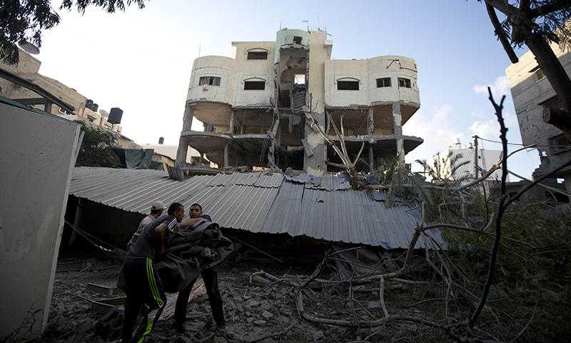 Palestinians inspect the house of senior Hamas official Mahmud al-Zahar after it was destroyed by an overnight Israeli air strike. — Photo by AFP