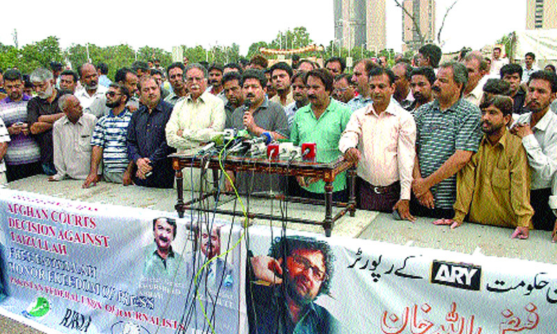 information Minister Pervaiz Rasheed joins journalists for a protest outside the National Press Club on Wednesday.